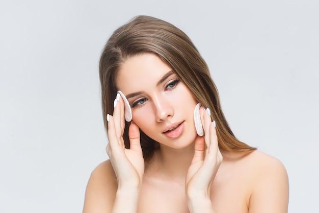 Giovane donna che si applica il fondotinta in polvere sul viso con un puff di spugna cosmetico