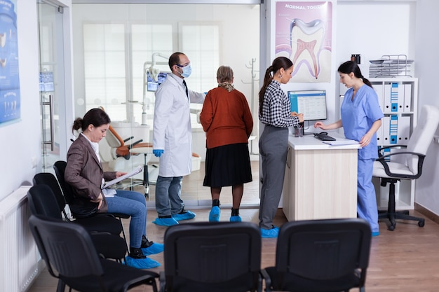 Young lady asking informations filling in stomatological form while patients talking sitting on chair in waiting area. people speaking in crowded professional orthodontist reception office.