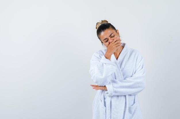 Giovane donna in accappatoio che copre la bocca con la mano e sembra assonnata