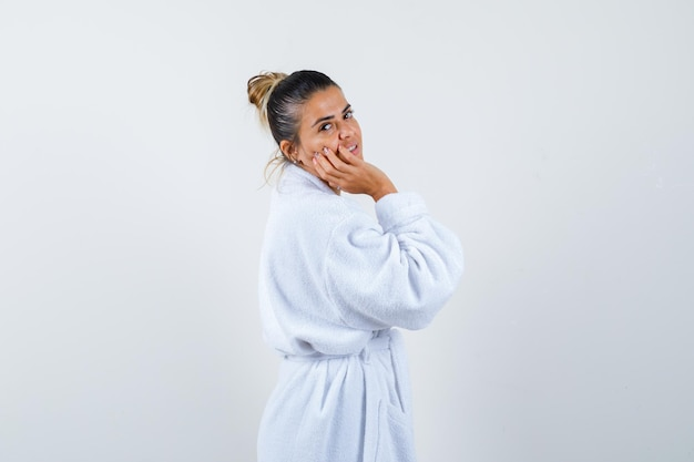 Young lady in bathrobe holding hand on cheek and looking positive