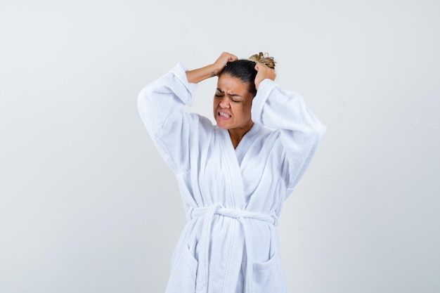 Young lady in bathrobe holding hands on head and looking annoyed