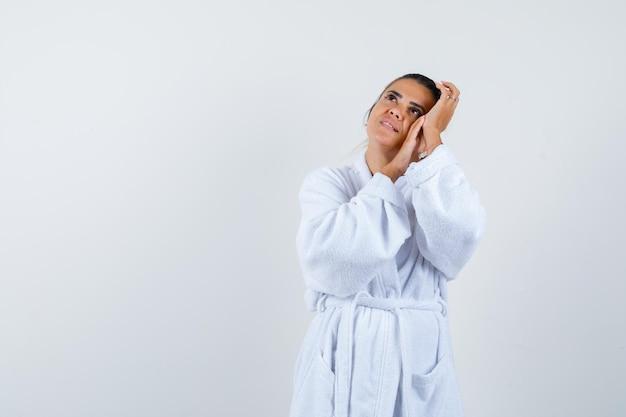 Giovane donna in accappatoio che si appoggia la guancia sulle mani e sembra pensierosa