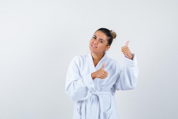 Giovane donna in accappatoio che mostra i pollici in su e sembra gioiosa