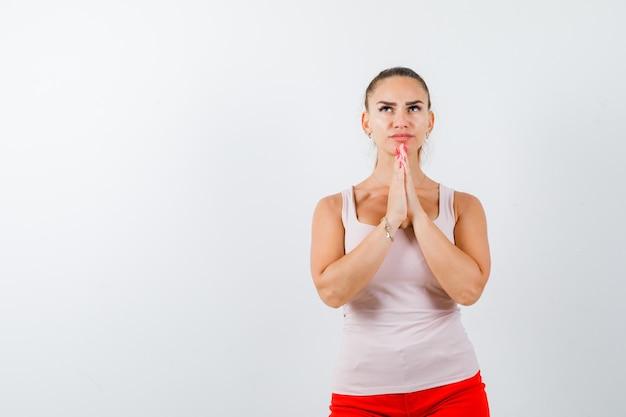 Giovane donna in canottiera beige tenendosi per mano nel gesto di preghiera e guardando speranzoso