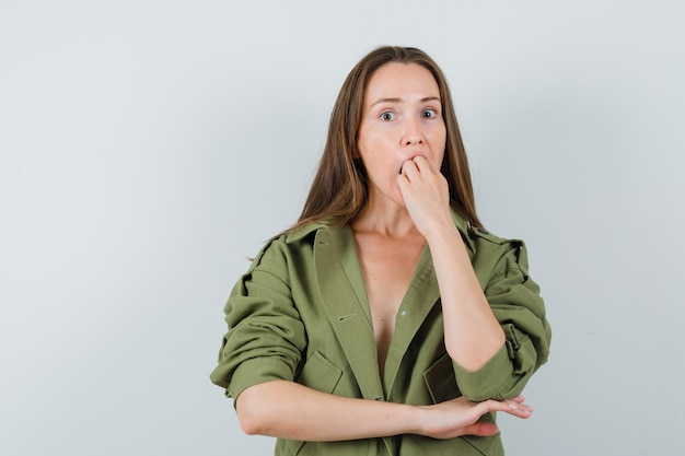 Young lady biting fist emotionally in green jacket and looking anxious