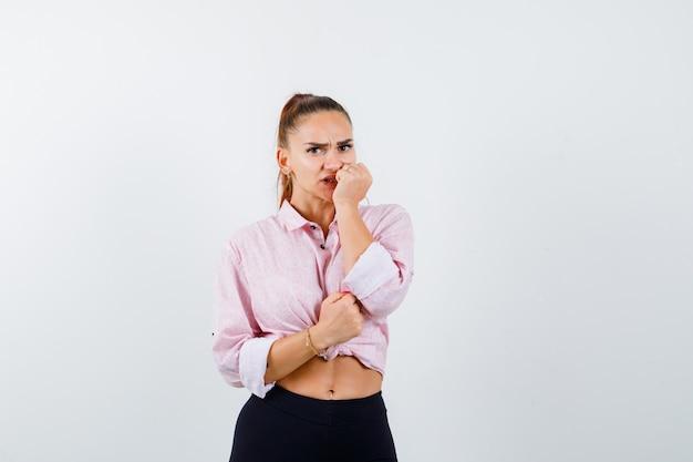Giovane donna che morde il pugno emotivamente in camicia e sembra spaventata. vista frontale.