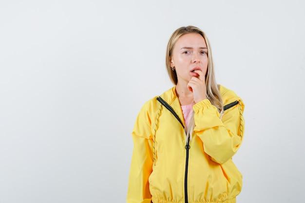 Tシャツ、ジャケットで指を噛み、困惑しているように見える若い女性