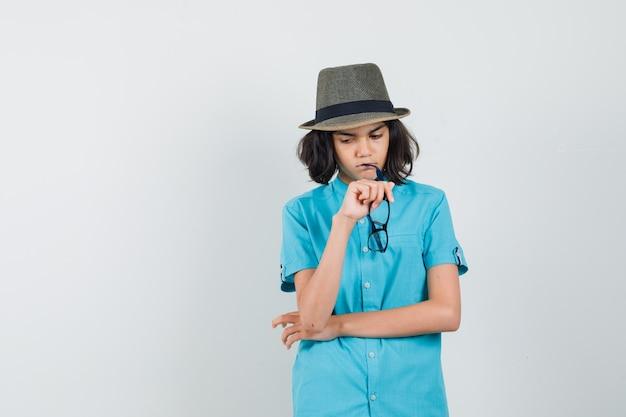 Giovane signora che si morde gli occhiali in camicia blu e sembra confusa