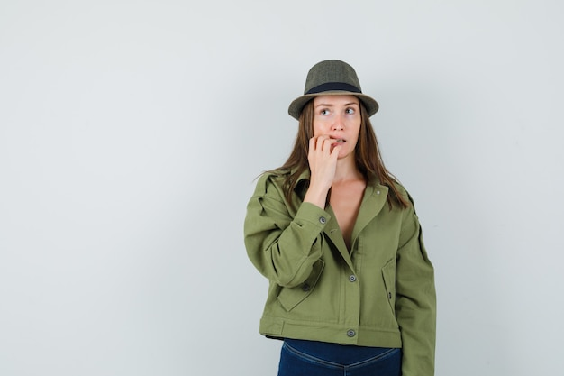Young lady biting her nails in jacket pants hat and looking hesitant