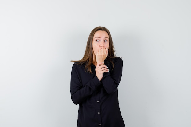 손톱을 물어뜯고 불안해하는 젊은 여성