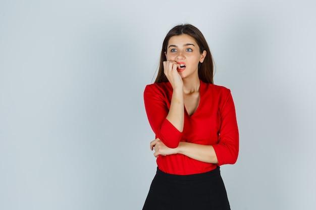 Giovane signora che morde le unghie in camicetta rossa, gonna e sembra spaventata