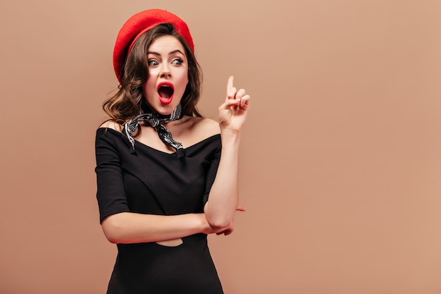 Young lady in black dress, red hat and scarf thought of new idea and shows with her index finger upwards.