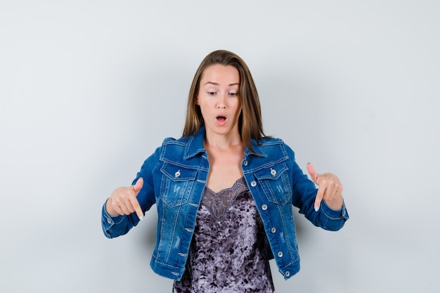Young lady in blouse, denim jacket pointing down and looking puzzled , front view.