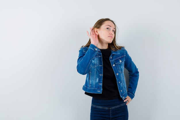 Young lady in blouse holding hand behind ear and looking curious , front view.