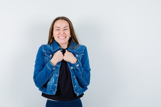 Giovane donna in camicetta, giacca che si tiene per mano sul petto e sembra allegra, vista frontale.
