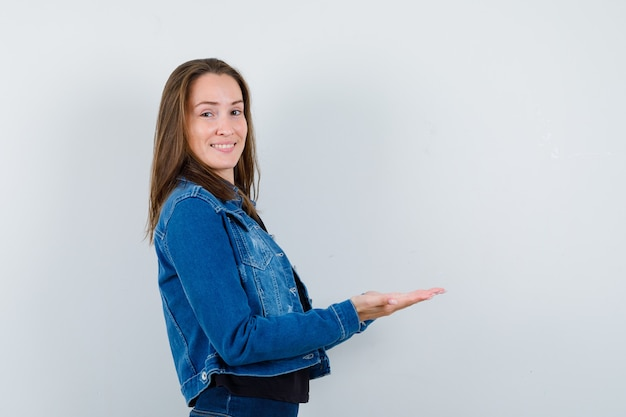 Giovane donna in camicetta, giacca che tiene le mani a coppa e sembra sicura.
