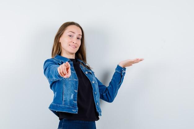 Giovane donna in camicetta, giacca che punta alla telecamera, mostra qualcosa e sembra sicura, vista frontale.