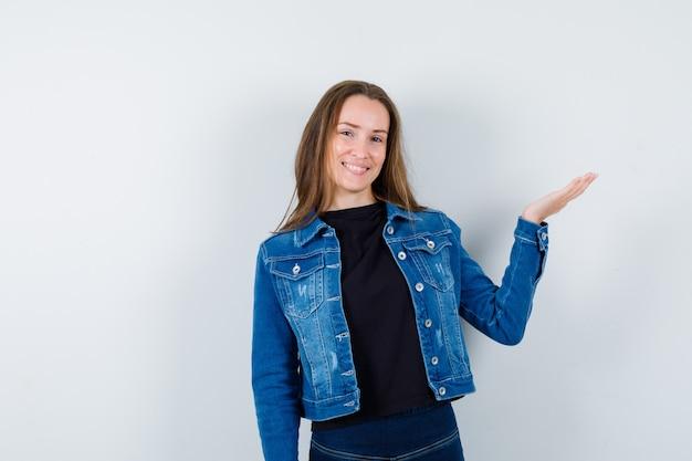 Giovane donna in camicetta, giacca che alza il palmo aperto e sembra allegra