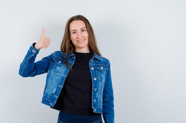 Giovane donna in camicetta, giacca che mostra pollice in su e sembra allegra, vista frontale.