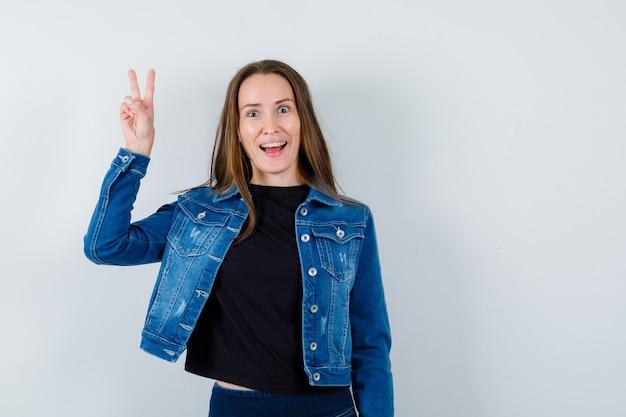 Giovane donna in camicetta, giacca che mostra il segno a v e sembra allegra, vista frontale.