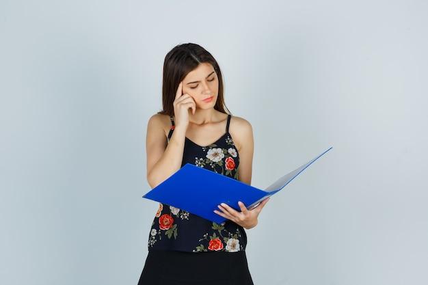 Giovane donna in camicetta che guarda la cartella, tiene il dito sulle tempie e sembra premurosa, vista frontale.