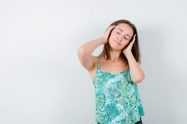 Giovane donna in camicetta che massaggia la testa e sembra rilassata, vista frontale.