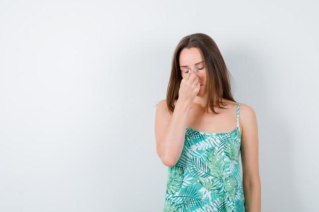 Giovane donna in camicetta che massaggia il ponte nasale e sembra esausta, vista frontale.