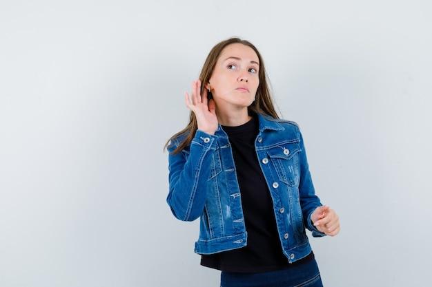 Giovane donna in camicetta che ascolta una conversazione privata e sembra curiosa, vista frontale.
