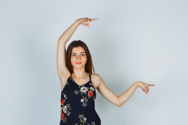 Giovane donna in camicetta che punta da parte e sembra allegra, vista frontale.