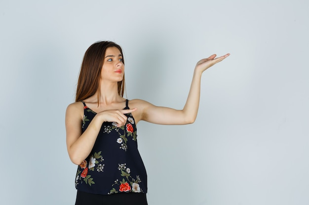 Giovane donna in camicetta che indica da parte mentre fa un gesto di benvenuto e sembra sicura, vista frontale.