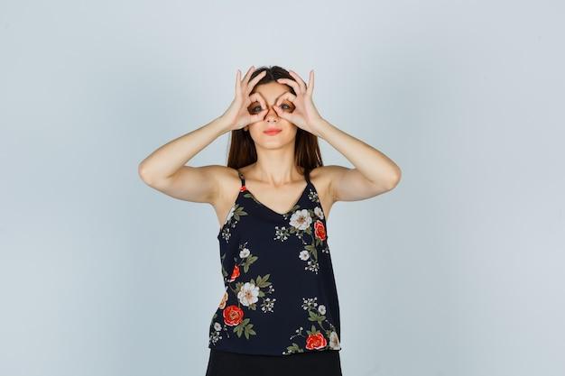 Giovane donna in camicetta che mostra il gesto degli occhiali e sembra curiosa, vista frontale.