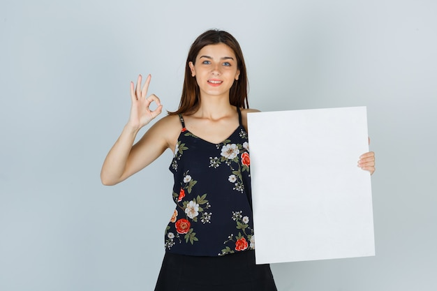 Young lady in blouse, skirt holding blank canvas, showing ok gesture and looking jolly , front view.