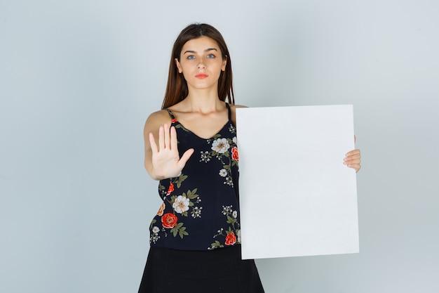 Giovane donna in camicetta, gonna con tela bianca, che mostra il gesto di arresto e sembra seria, vista frontale.