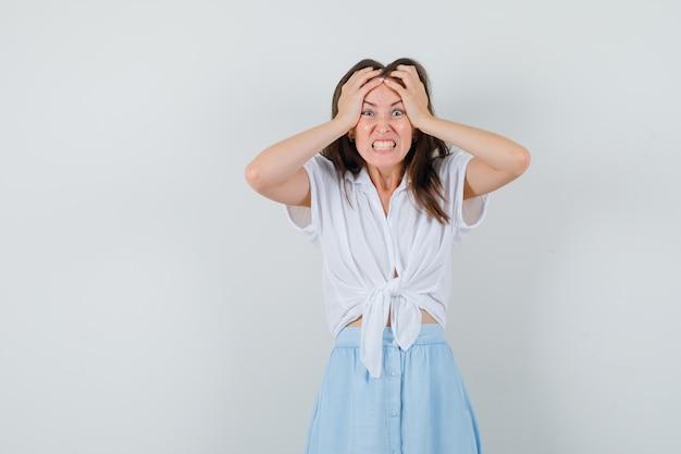 Giovane donna in camicetta, gonna che si tiene per mano sulla sua testa e sembra annoiata