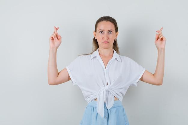 Giovane donna in camicetta e gonna tenendo le dita incrociate e guardando perplessa