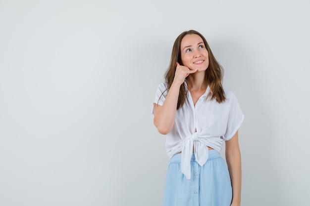 Giovane donna in camicetta e gonna che mostra il gesto del telefono e sembra speranzosa