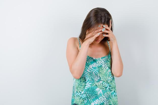 Giovane donna in camicetta con le mani sulla testa e guardando esausto, vista frontale.