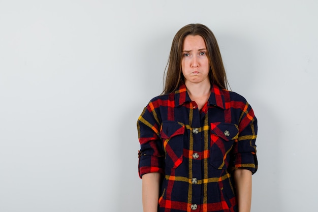 Молодая леди дует щеки в повседневной рубашке и выглядит озадаченно, вид спереди.