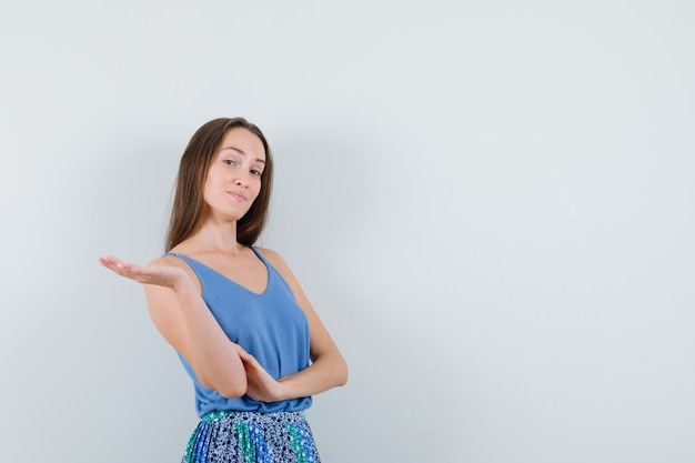 Young lady in blue blouse,skirt spreading her palm aside and looking self-confident , front view.