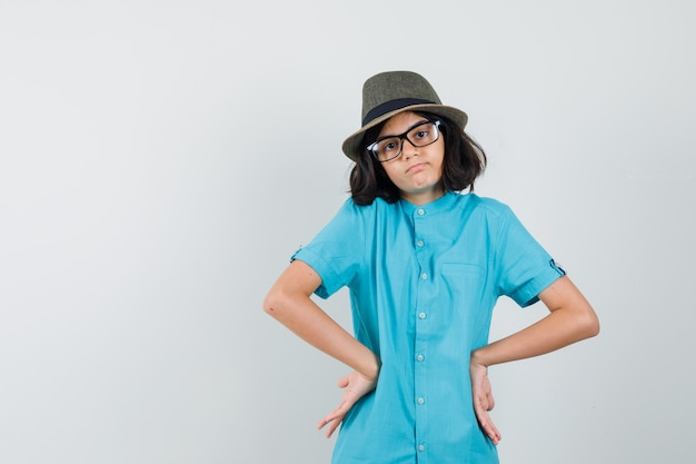 Young lady in blue shirt, hat, glasses standing with hands on waist and looking sad