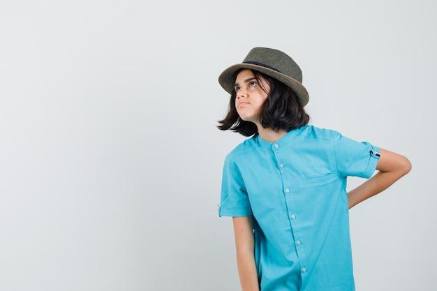 Giovane donna in camicia blu, cappello che tiene la mano sulla sua spina dorsale e che sembra turbata
