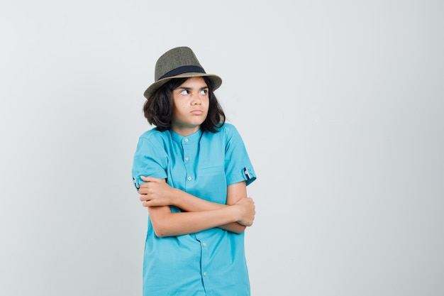 Young lady in blue shirt, hat hugging herself and looking uncomfortable