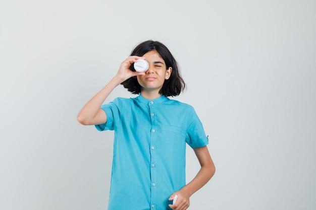 Giovane donna in camicia blu che tiene una bottiglia di pillole sopra l'occhio e sembra divertente