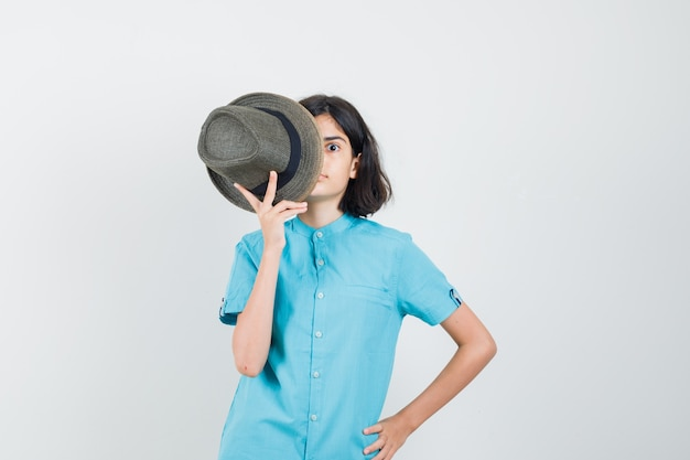 Young lady in blue shirt holding hat on her half of face and looking weird