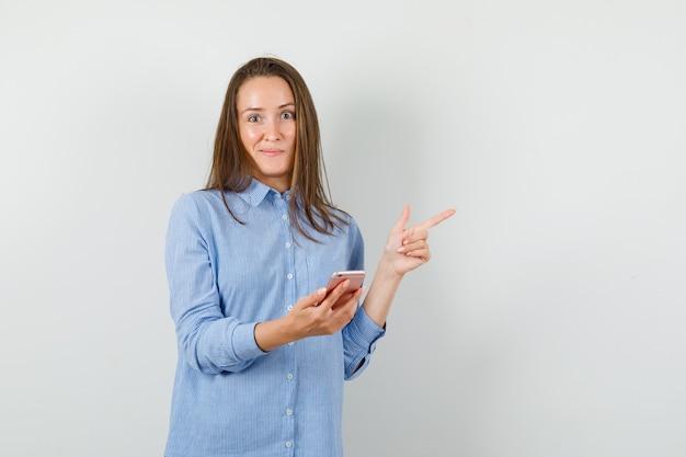 Giovane donna in camicia blu che tiene il telefono cellulare mentre punta lontano e sembra curioso
