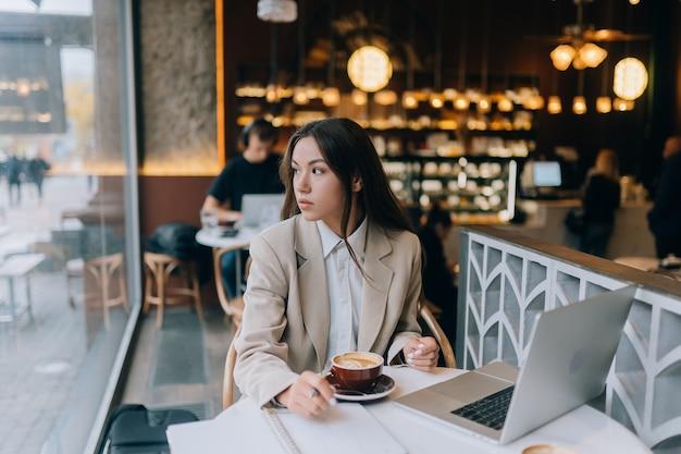 Молодая дама просматривает интернет в кафе