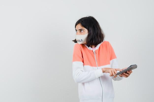 Giovane donna che calcola con la calcolatrice in felpa con cappuccio, maschera per il viso e sembra concentrata.