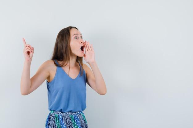 若い女性がブラウス、スカートで大きな声で誰かに電話をかけ、心配そうに見えます。正面図。テキスト用のスペース