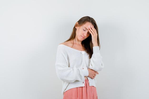 Giovane donna in cardigan e gonna tenendo la mano sulla fronte guardando pensieroso isolato