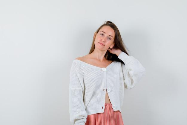 Giovane donna in cardigan e gonna tenendo la mano sul collo guardando fiducioso isolato